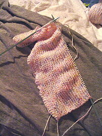 Flat knitting. The loops on the metal needle are the active stitches, and the yarn coming out of the knitting on the right is the working yarn.