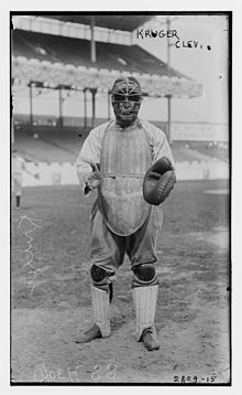 A man wearing a baseball uniform and full catcher's gear (facemask, catcher's mitt, chest protector, and leg guards) stands poised to catch a ball.