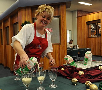 Eggnog - A woman serves commercially prepared eggnog to US military personnel at a Christmas party.