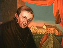 A painting of a priest with thin brown hair facing his left in front of a parted curtain that reveals a series of buildings in the background.