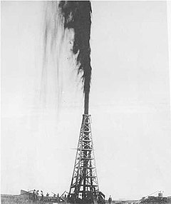 Black-and-white photograph of an oil derrick with a gusher of oil shooting from the top