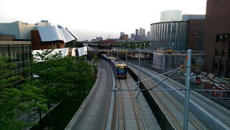 Metro Green Line (Minnesota) - An eastbound Green Line train just across the Washington Avenue Bridge traveling past the Weisman Art Museum on the  University of Minnesota's East Bank
