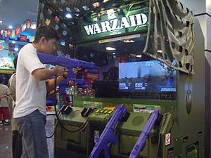 Arcade game - A man playing arcade game using a light gun in Jakarta, Indonesia
