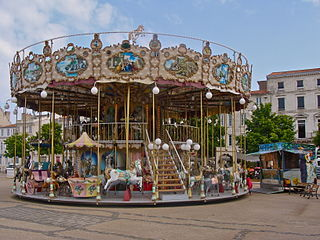 Carousel amusement ride consisting of a rotating circular platform with seats for riders