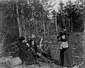 Man and woman sitting on log in woods with woman standing in front of them, ca 1898-1899 (WASTATE 2508).jpeg
