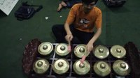 Gambar:Man demonstrating arrangement of sundanese gamelan bonang gong in pairs of ascending notes.ogv