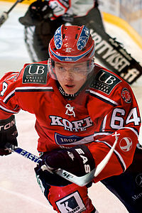 An ice hockey player skating towards the camera with his ice hockey stick raised of the ice. He is wearing a red helmet and uniform.