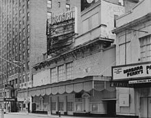 "Daytime. A plain theatre front is seen from the sidewalk, at an angle, with an electrical sign above showing the theatre's name. No play is advertised. The cornice is dirty and in disrepair. Next door (at right), part of another theatre is shown, with a play advertised on its marquee, and two ""Post No Bills"" signs at eye level. The left of the image shows part of a large hotel, with three people near the entrance."