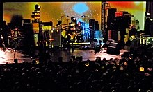 A five-piece rock band performing onstage against a psychedelic style yellow backdrop. Audience members facing the stage are visible in the foreground; various equipment including amplifiers, effect pedals, monitors and guitars are visible in the background.