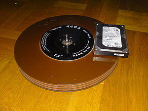 "Disk pack - Disk pack manufactured by Nashua, USA, without its protective cover. A 3.5"" modern hard drive is shown for comparison."
