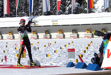 A woman in predominantly black winter sportswear, looking concentrated, holds a rifle which points into the sky. She stands on a red mat and a photographer with a large object lens kneels on the right hand side. Parts of a shooting range covered in snow can be seen in the background.