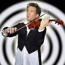 Man dressed in a tailcoat and open-necked white shirt, playing a violin