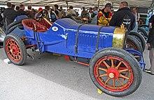 Photo d'une voiture de course à deux places de couleur bleue dans un stand.