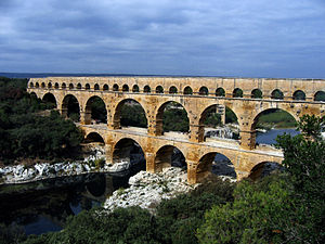 Roman aqueduct - The multiple arches of the Pont du Gard in Roman Gaul (modern-day southern France). The upper tier encloses an aqueduct that carried water to Nimes in Roman times; its lower tier was expanded in the 1740s to carry a wide road across the river.