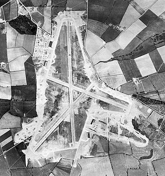 RAF Harrington - Aerial photograph of Harrington airfield looking north, the main runway runs vertically, 22 April 1944. Note the many aircraft of the 801st Bombardment Group on the various hardstands, also one appearing to be taking off on the main runway.