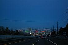 Dusk view of a freeway descending into a neon lit cityscape.