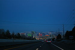 Dusk view of a freeway descending into a neon lit cityscape