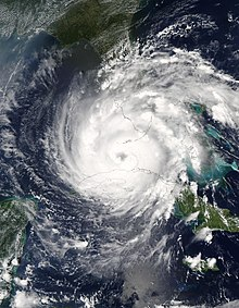Satellite image of a strengthening hurricane passing between two landmasses. The hurricane has also developed an eye.