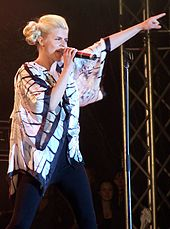 Young blonde woman singing onstage, pointing upwards