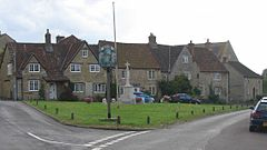 Street scene. Triangular area of grass with village sign on wooden post and stone cross behind. Stone houses with tiled roofs in the background.