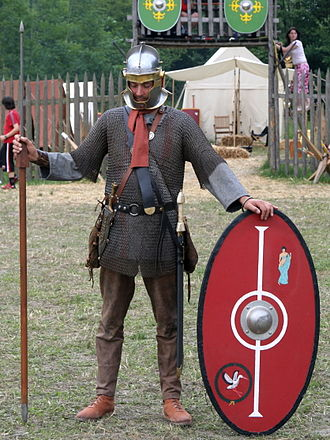 "Late Roman army - Reenactor wearing the typical equipment of a late 3rd-century foot soldier. The helmet is a Niederbieber type, with cross-pattern reinforcing ridges on the top of the bowl, and cheek-guards which can be fastened together. The sword is a spatha (median blade length 900 mm/36 inches), used by the cavalry only in the 1st and 2nd centuries. This soldier carries a spiculum, a heavy pilum-type javelin. Note the chain mail (lorica hamata) shirt and oval shield. Clothing consisted of a long-sleeved tunic, trousers and boots. The equipment of a 4th-century infantryman was very similar to the 3rd century, save that the spiculum was usually replaced by a heavy thrusting-spear (hasta) and the helmet was predominantly of the ""Intercisa type""."