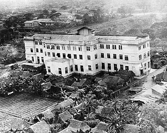 Santo Tomas Internment Camp - One of the principal buildings housing internees at Santo Tomas was the Education building (now UST Hospital building). Shanties and vegetable gardens can be seen near the building and the wall of the University compound is in the background.