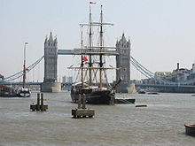 A sailing ship sits moored on the River Thames, with a large bridge in the background