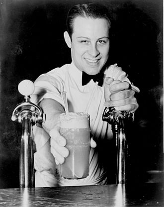 "Soda fountain - A ""soda jerk"" serving an ice cream soda.  His left hand rests on the tap of a soda fountain (1936)"