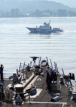 Smaller military boat passing a larger one