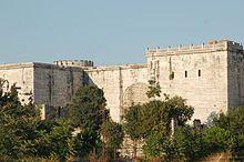 Foto eines mit Marmor bedeckten Torkomplexes mit zwei quadratischen vorspringenden Türmen und einem eingemauerten Tor