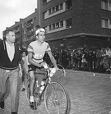 Photographie en noir et blanc montrant un cycliste sur son vélo, un homme se tenant à côté.