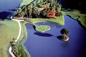 Greenskeeper - The famous 17th hole of the TPC at Sawgrass Stadium Course. Greenskeepers keep ponds free of detrimental aquatic weeds and sometimes dye water blue.