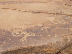A sandstone slab in horizontal position, cracked in about half. The front piece features engravings of two antelopes. Four circles overlay the slab, two attached to the left antelope which probably depicts a Kudu, and two near the left antelope.