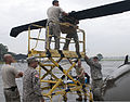 U.S. Army Lt. Col. Roger Pukahi, right, the aviation officer in charge, and Chief Warrant Officer 3 John Yim, left, the safety officer, help the crew with Detachment 1, Charlie Company, 207th Aviation Regiment 130617-Z-NO327-015.jpg