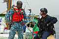 U.S. Coast Guard Chief Maritime Enforcement Specialist Rob Wills, right, with the Maritime Security Response Team, and Gambian Navy Lt. Simon Peter Mendy discuss tactical operations while aboard a fishing vessel 120619-N-GN377-060.jpg
