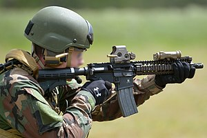Modular Integrated Communications Helmet - A US Marine CSO practices firing his carbine at the Grafenwoehr Training Area's shooting range.