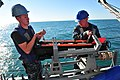 U.S. Navy Mineman (MN) Seaman Brett Walker, left, and MN2 Anthony Killen, assigned to MCM Crew Dominant and deployed aboard the mine countermeasures ship USS Gladiator (MCM 11), lift and place a SeaFox portable 130117-N-CG436-160.jpg