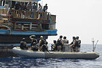 U.S. Sailors with a visit, board, search and seizure team aboard USS Gettysburg (CG 64) and U.S. Coast Guardsmen from Law Enforcement Detachment 409 arrive to assist crewmembers aboard a Yemeni dhow in the Gulf 090526-N-VQ138-071.jpg