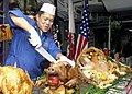 US Navy 021128-N-1356A-006 Master Chief Mess Management Specialist prepares for the first slice of a baked pig to be served as Thanksgiving dinner.jpg