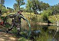 US Navy 050421-N-1722M-119 Utilitiesman 2nd Class Brian Cox, assigned to Naval Mobile Construction Battalion Two Five (NMCB-25) based at Fort McCoy, Wis., throws a suction hose into a local reservoir.jpg