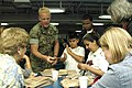 US Navy 050712-N-1397H-026 U.S. Marine Corps Sgt. Jeremey D. Myrick explains to civilians aboard the amphibious assault ship USS Peleliu (LHA 5) what an MREs (Meal Ready to Eat) are and their importance to the military.jpg