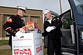 US Navy 081218-1057H-N-303 Marine Corps Sergeant Jeffrey Kellum hands a box of donated toys to Hospital Corpsman 2nd Class Christopher Long.jpg