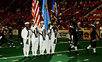 Cox Convention Center - Members of the Navy Color Guard join the Oklahoma City Yard Dawgz players on the field at Cox Convention Center during the opening ceremony