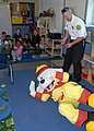 US Navy 091005-N-9860Y-003 Cliff Foley, a Navy Region Northwest Fire and Emergency Services fire inspector, and Sparky the Fire Dog demonstrate stop, drop and roll to School Age Care Programs students.jpg