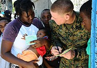 US Navy 100204-N-5268S-129 ance Cpl. Benjamin Rauschenberg, a linguist from the 22nd Marine Expeditionary Unit (22nd MEU), helps a young Haitian woman fill out her immunization card at a clinic