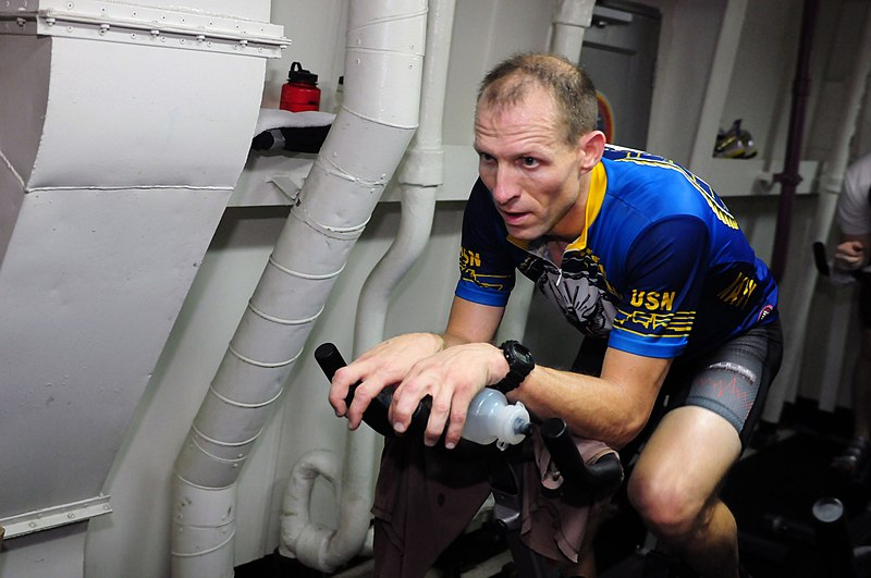 File:US Navy 101107-N-5503T-099 Lt. j.g. Chad Haack cycles during the simulated bicycle course portion of a shipboard triathlon aboard the aircraft carr.jpg