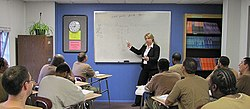 A woman standing at the front of a classroom pointing to fractions on a whiteboard. There are eleven men picture sitting at desks in front of her