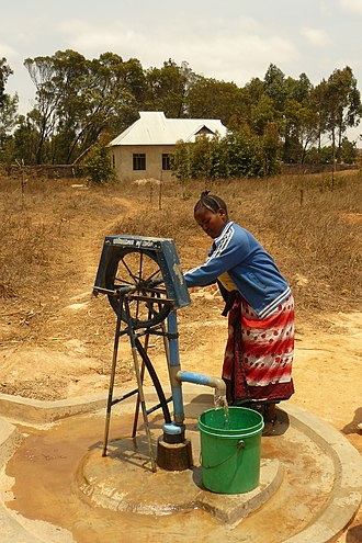 Self-supply of water and sanitation - A person using a rope pump in rural Tanzania to obtain groundwater from a well