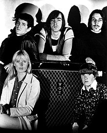 Black and white photograph of five people posed around a guitar amplifier