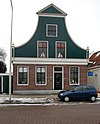foto van Bakstenen huis met ingezwenkt houten voorschot met verdiepte zijpilasters en bekronend fronton